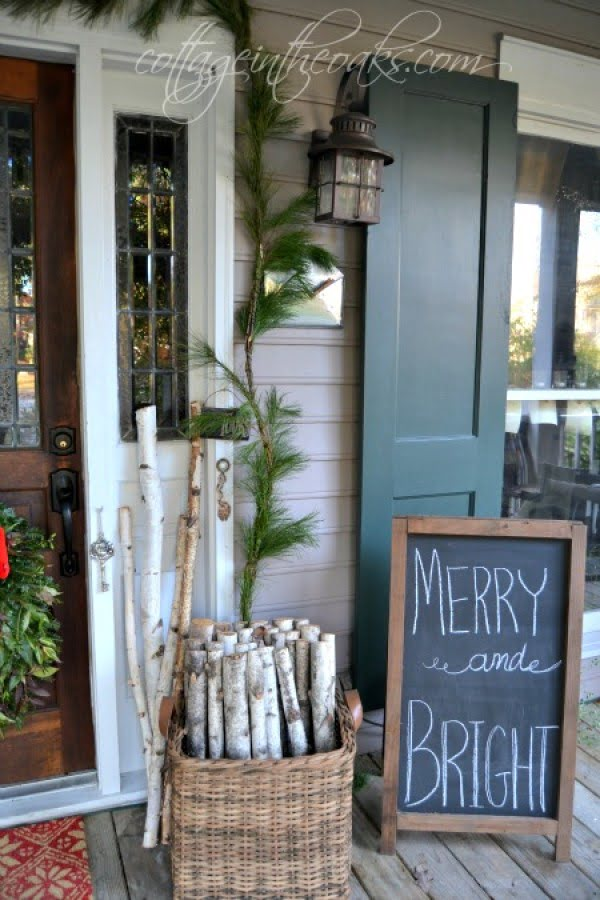 Simple but attractive Christmas porch decor with chalkboard and firewood