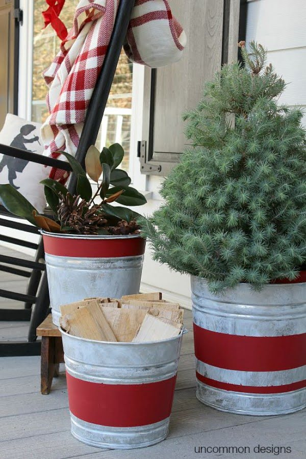Love the idea for Christmas porch decor with striped galvanized buckets