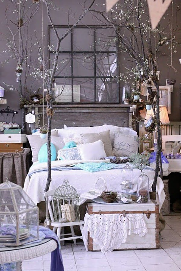 Love the rustic decor of this bedroom with dried tree branch bed posts