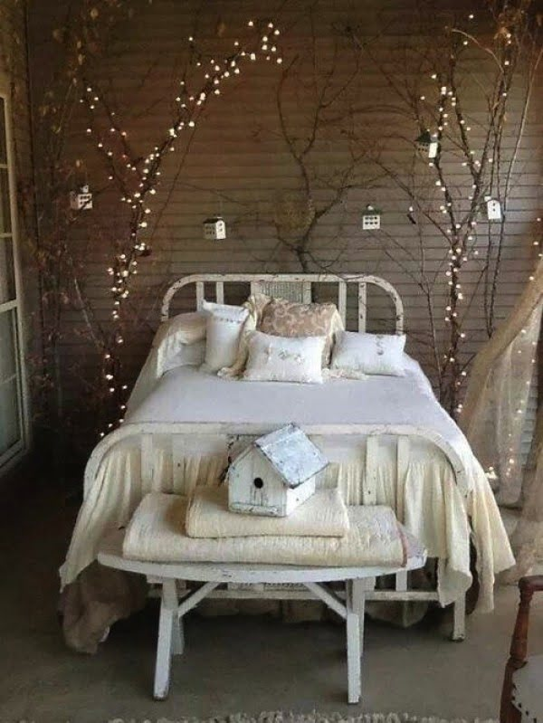 Love the bed decoration with tree branches and fairy lights
