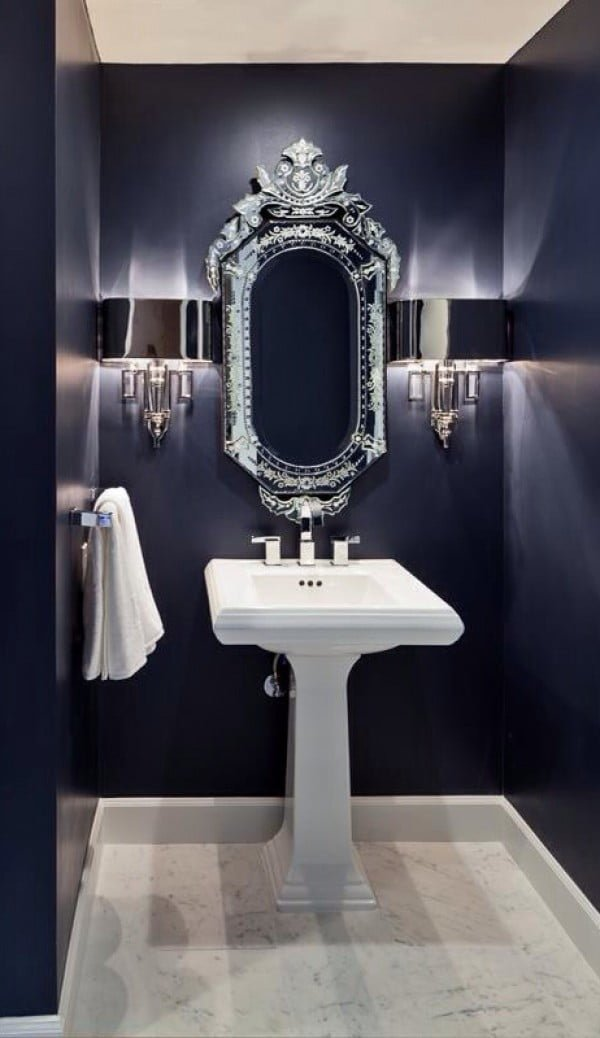 Love the navy blue bathroom walls and silver mirror frame