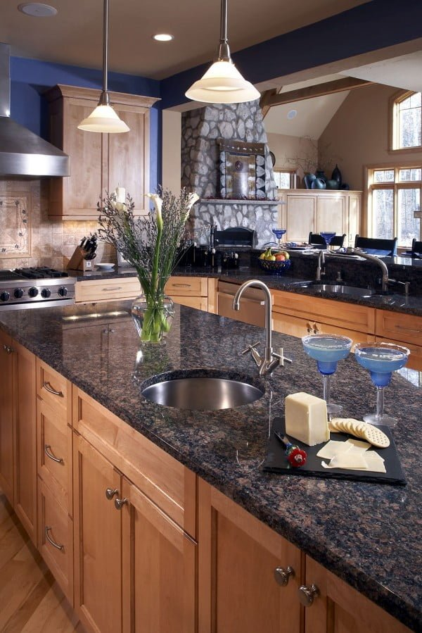 Tan brown  countertops work so well with blue accent walls. Love this  decor!