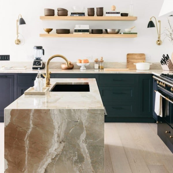You have to see these dark blue kitchen cabinets with marble counters and natural wood accents. Love it!