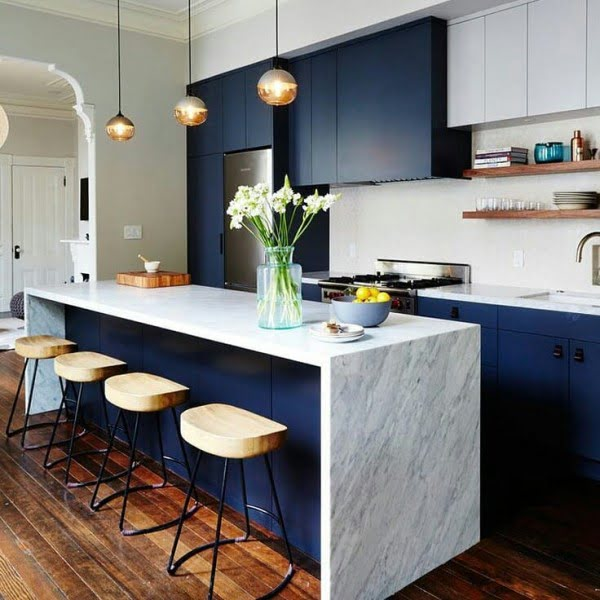 You have to see these blue kitchen cabinets with marble countertops and natural wood accents. Love it!