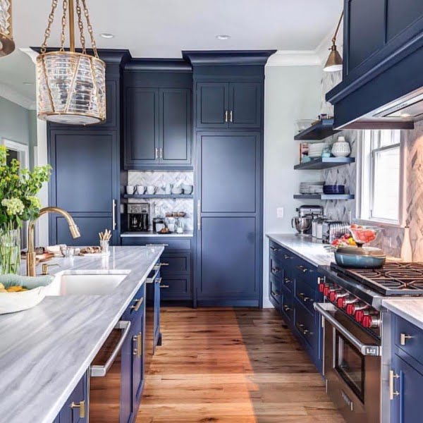 You have to see these blue kitchen cabinets with marble countertops and hardwood floor. Love it! #KitchenDesign #HomeDecorIdeas