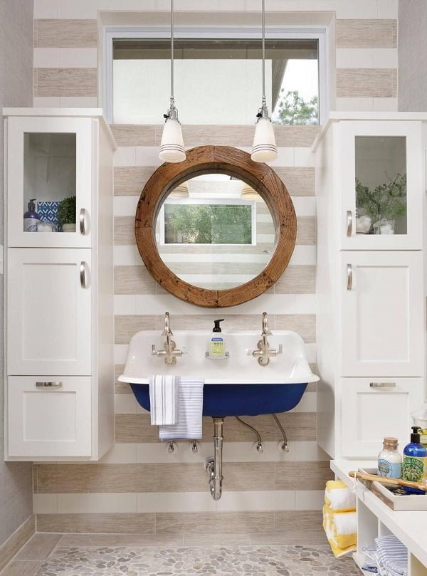 Love this bathroom decor with a round mirror and navy accent sink. Awesome   decor!