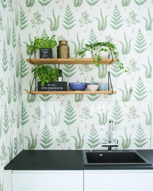 Check out this unusual kitchen design with minimalist shelving and greenery. Love it!