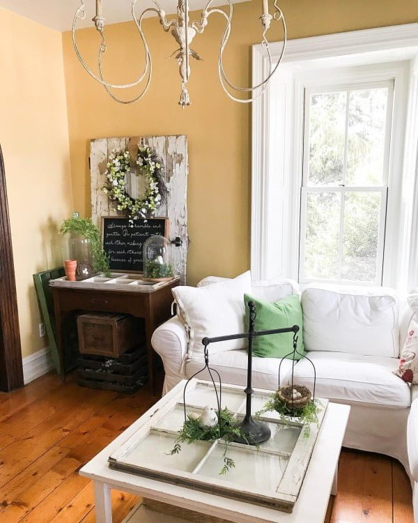 living room decor idea with a vintage chandelier and a coffee tale made from an old window frame. Love it!