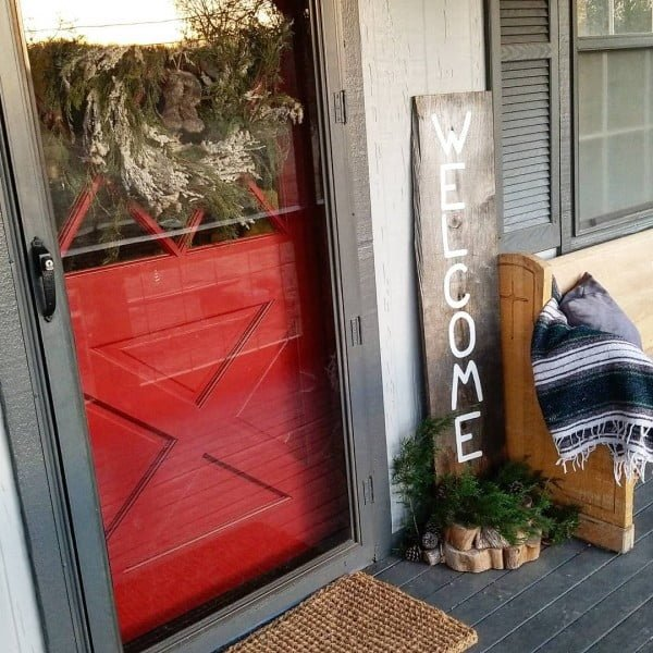 Check out this  porch decor idea with greenery arrangements and a  sign. Love it!