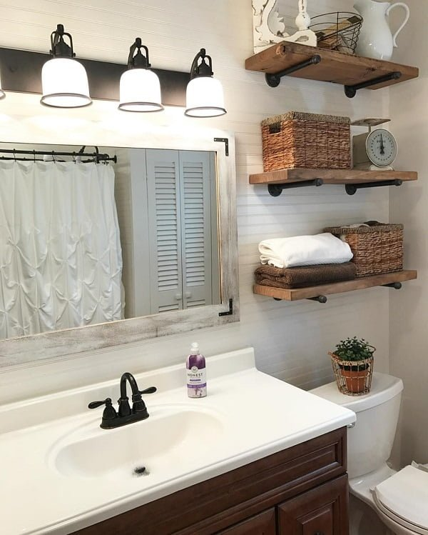 100 Cozy Rustic Farmhouse Bathroom Decor Ideas You Can Easily Copy - You have to see this #farmhousebathroom decor idea with multiple wooden shelves and attainable openess. Love it! #BathroomDecor #HomeDecorIdeas
