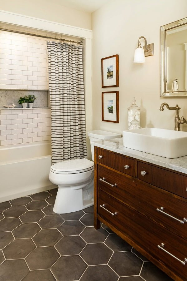 100 Cozy Rustic Farmhouse Bathroom Decor Ideas You Can Easily Copy - You have to see this bathroom decor idea with wooden cabinets and photo frames as well as a vessel sink. Love it!