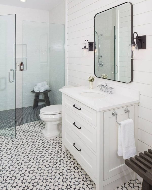 100 Cozy Rustic Farmhouse Bathroom Decor Ideas You Can Easily Copy - You have to see this #farmhousebathroom decor idea with a wooden shower stool and multi-purpose white sink cabinet. Love it! #BathroomDecor #HomeDecorIdeas