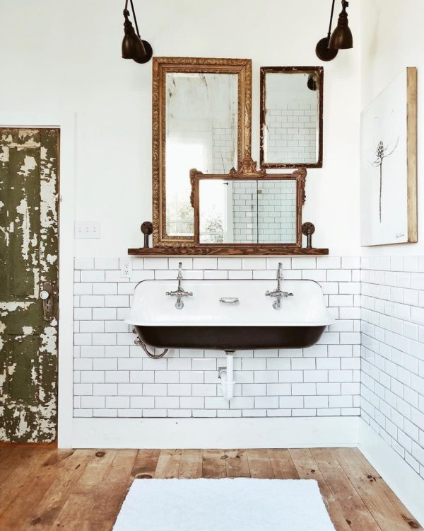 100 Cozy Rustic Farmhouse Bathroom Decor Ideas You Can Easily Copy - You have to see this #farmhousebathroom decor idea with hardwood flooring, white brick tile wall and rustic entrance door. Love it! #BathroomDecor #HomeDecorIdeas