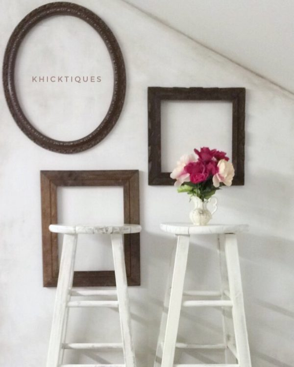 You have to see this #farmhouse decor idea with a slanted backrgound wall and editorial blend of wooden photo frames. Love it! #FarmhouseDecor #HomeDecorIdeas