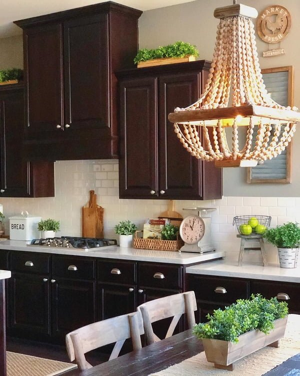 You have to see this #farmhousekitchen decor idea with black and silver cabinets and handmade wood chandelier. Love it! #FarmhouseKitchen #HomeDecorIdeas