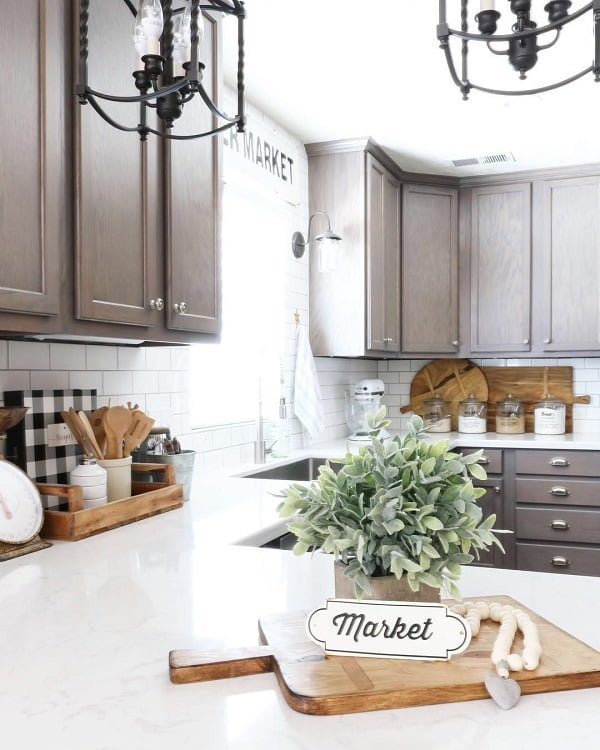 You have to see this #farmhousekitchen decor idea with white brick-tile walls and two iron chandeliers. Love it! #FarmhouseKitchen #HomeDecorIdeas