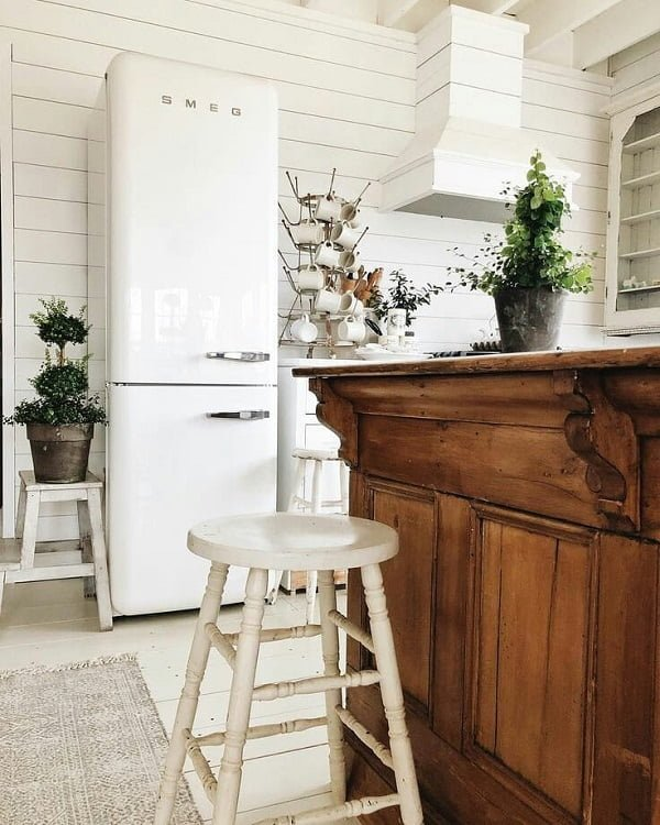 You have to see this #farmhousekitchen decor idea with pedestal stands and white hardwood walls. Love it! #FarmhouseKitchen #HomeDecorIdeas