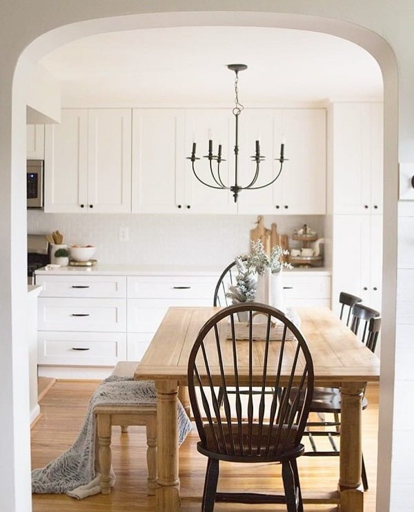 You have to see this #farmhousekitchen decor idea with dark hardwood chairs and castle-inspired chadelier. Love it! #FarmhouseKitchen #HomeDecorIdeas