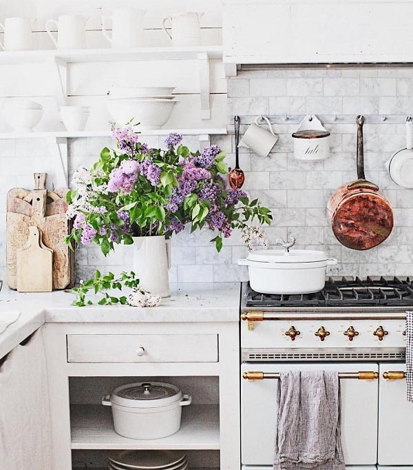 You have to see this #farmhousekitchen decor idea with open white cabinets and dynamic kitchenware. Love it! #FarmhouseKitchen #HomeDecorIdeas
