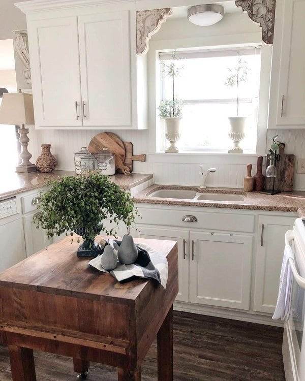 You have to see this #farmhousekitchen decor idea with statement outdoor window and dark hardwood floors. Love it! #FarmhouseKitchen #HomeDecorIdeas