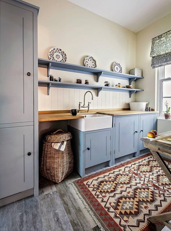 You have to see this #farmhousekitchen decor idea with wall-to-wall wood shelves and medium hadrwood kitchen counters. Love it! #FarmhouseKitchen #HomeDecorIdeas