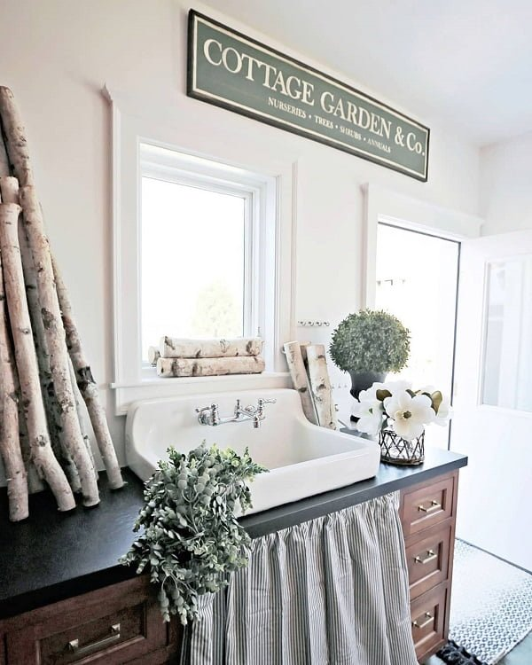 100 Inspiring Farmhouse Sink Ideas for the Kitchen and Bathroom - You have to see this sink decor idea with widespread silver faucet and romantic curtain-covered storage cabinet just beneath the sink itself. Love it!