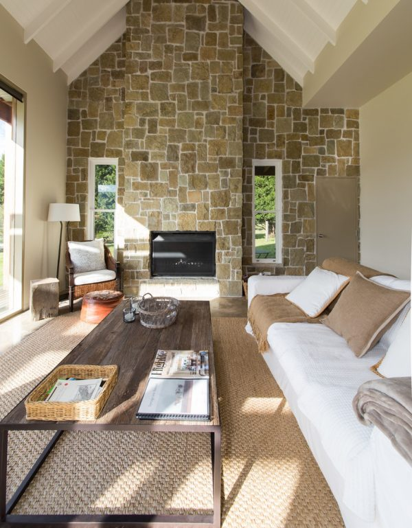 living room decor idea with detailed stone wall and barn-styled coffee table. Love it!