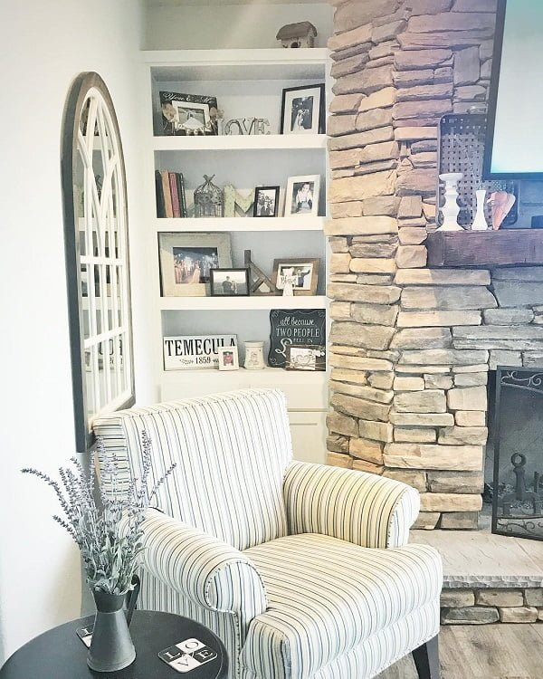 living room decor idea with internal window overlooking the impactful stone fireplace. Love it!