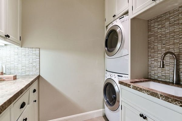 100 Fabulous Laundry Room Decor Ideas You Can Copy - You have to see this #laundryroom decor idea with playful bamboo wall details and thoughtfully stacked washer/dryer. Love it! #LaundryRoomDecor #HomeDecorIdeas