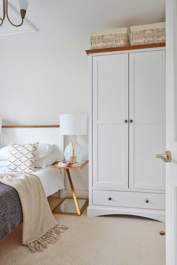 You have to see this #modernfarmhouse decor idea with white nightlamp and top-of-the-closet storage baskets. Love it! #ModernFarmhouseDecor #HomeDecorIdeas